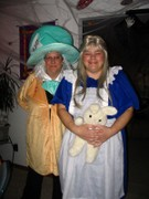 customer wearing plus size Alice in Wonderland Halloween costume in dark blue with Mad Hatter costume and white rabbit plush toy
