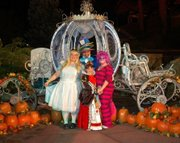 customer wearing plus size Alice in Wonderland Halloween costume with Queen of Hearts and Mad Hatter and Cheshire Cat at Disney's Not So Scary Halloween celebration