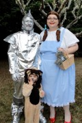 customer wearing Dorothy plus size Halloween costume from the Wizard of Oz with ruby slippers, also Tin Woodsman and Cowardly Lion