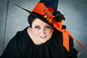 customer wearing plus size Renaissance Harvest Witch Halloween costume with solid orange skirt modeling the blackbird hat with autumn flowers and foliage