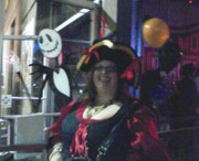 customer wearing plus size Renaissance Sexy Pirate Wench Halloween costume in red with black lace and buccaneer captain hat in front of Jack Skellington from Nightmare Before Christmas
