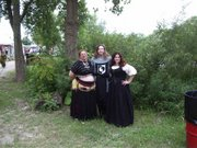 customer wearing plus size Renaissance historical gown dress outfit with black corset bodice black skirt and white peasant shirt at faire