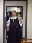 customer wearing plus size Renaissance gown dress with black corset bodice skirt and white peasant shirt chemise with gold dragon