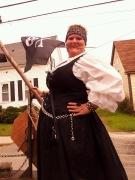 customer wearing plus size Renaissance Starter Package dress gown Halloween costume in black with white peasant shirt as pirate with skull and crossbones flag