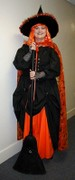 customer wearing plus size Renaissance Starter Package in solid black with additional solid orange skirt as witch with cape and hat and gloves and broom