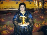 customer wearing plus size Renaissance Vampire Spider Web Witch Halloween costume in purple and silver holding first place trophy from costume contest
